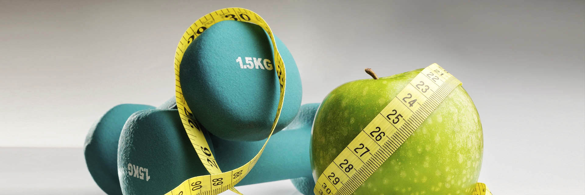 Apple, measuring tape, and dumbbells weights