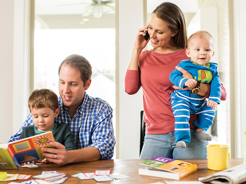 Young Mother Holding Baby While Dad Reads a Book